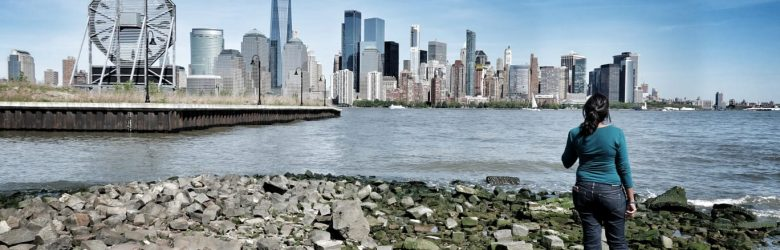 woman on rocky beach looking out at new york city skyline