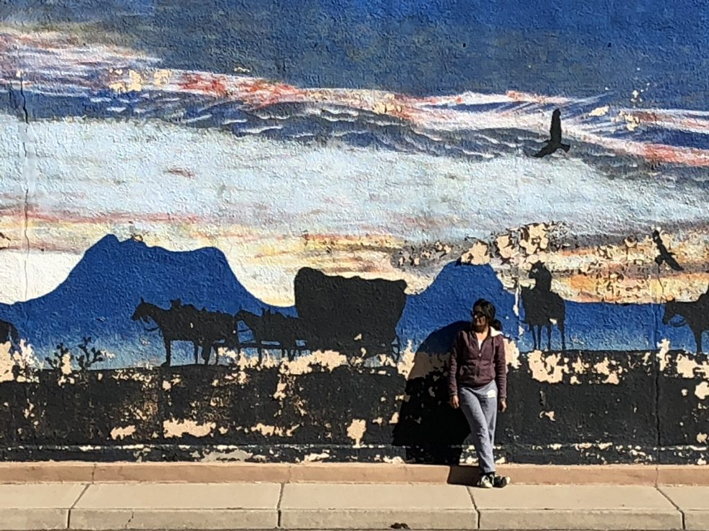 Woman standing in front of mural of cowboys, wagon scene