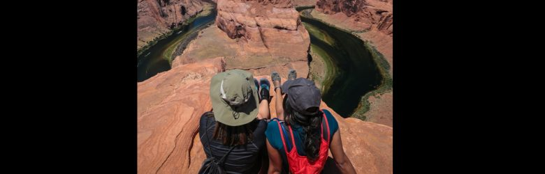 Two women sit on red rocks overlooking meandering river