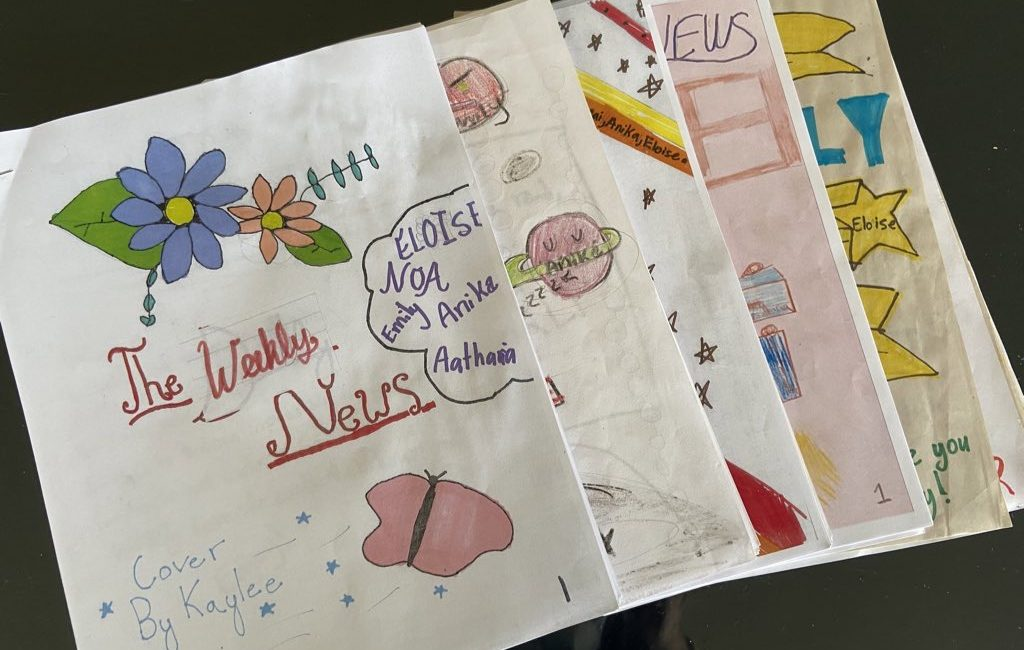 "hand-drawn ""Weekly News,"" with children's writing, five issues laid out"