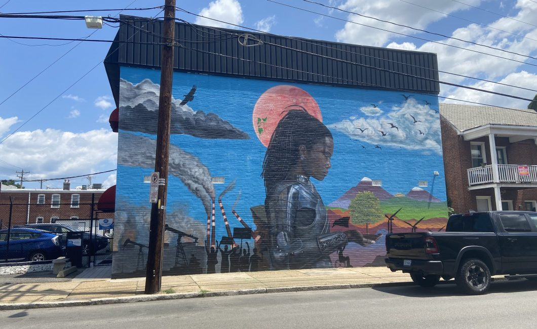Image of mural on side of a wall, showing industrial scenes with a Black woman in futuristic armor holding a tree tward a blue sky, mountain scene